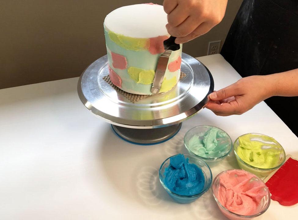 adding green buttercream to cake