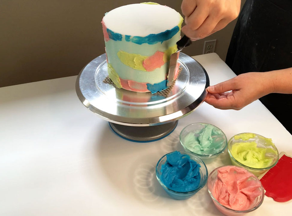 adding dark blue buttercream with icing knife